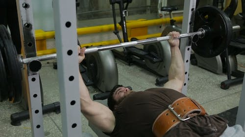 Powerlifter Strogman Picks Up the Bar Lying on the Bench