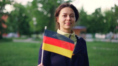 Portrait of Cheerful Young Woman Waving Official German Flag