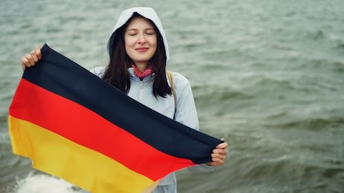 Portrait of Pretty German Woman Proud Citizen Holding Official Flag of Germany