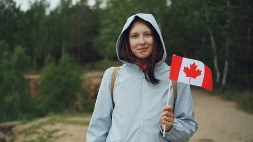 Portrait of Female Traveller Pretty Girl Holding Canadian Flag, Smiling and Looking at Camera with