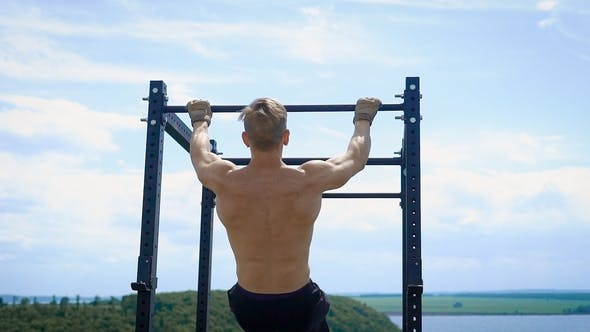 Thumbnail for Young Muscular Sportsman Is Lifting His Body Holding Crossbar Outdoors in Summer Day