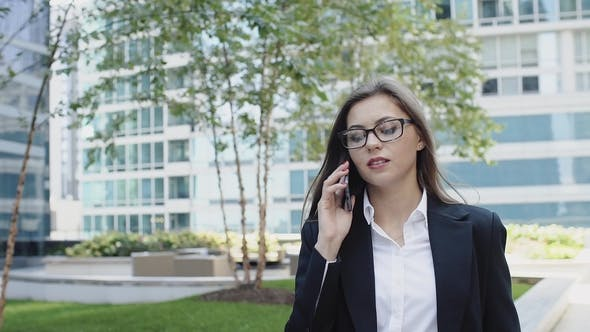 Attractive Lady in Business Suit Talking on Phone Outdoors Near Modern Buildings