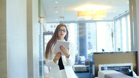 Thumbnail for Attractive 30s Girl with Glasses in Formalwear Holding Tablet PC in Big Lighted Office