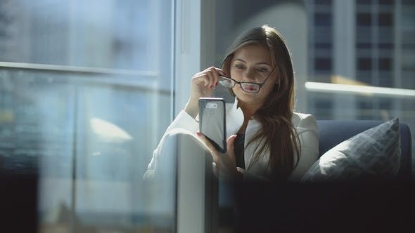 Is Concentrated Girl Uses Her Phone Sitting in Soft Chair Near Big Window