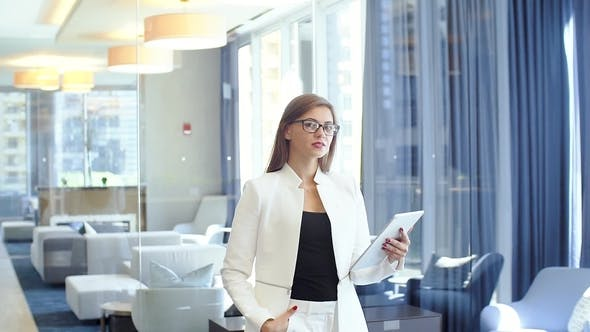 Thumbnail for Young Beautiful Businesswoman Standing with Tablet PC in Hands in the Middle of Office