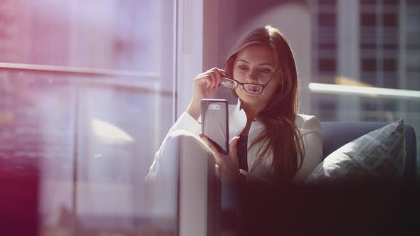 Thumbnail for Elegant Beautiful Woman with Glasses in Hand Uses Smartphone in the Office