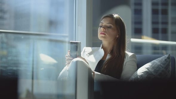 Thumbnail for Attractive Young Girl in Business Suit Sitting Near Big Window and Using Her Smartphone