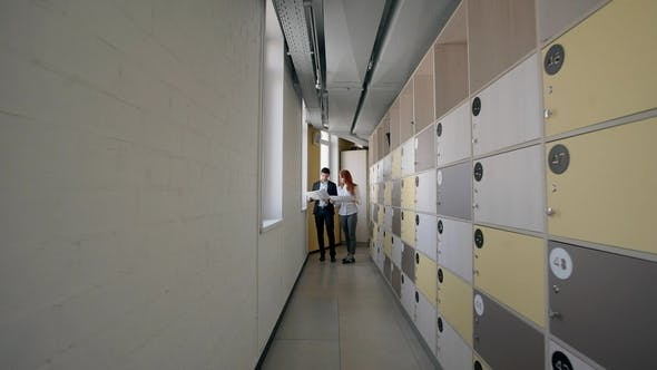 Thumbnail for Young Man and Woman Discussing Investment Project Standing in Corridor of Company