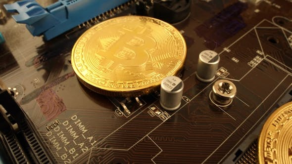 Cover Image for Gold Bit Coin BTC Coins on the Motherboard. Bitcoin Is a Worldwide Cryptocurrency