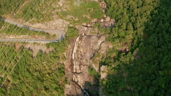 Drone Over Road And Rocky Waterfall In Forest