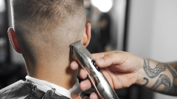 Thumbnail for Tattoed Barber Makes Haircut for Customer at the Barber Shop By Using Hairclipper, Man's Haircut