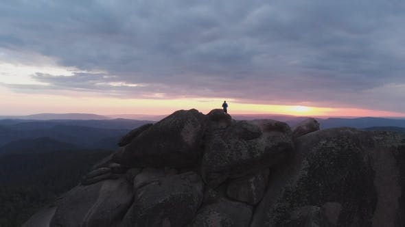 Thumbnail for Aerial View of the Lonely Man Standing on Top of a Cliff and Enjoying the Sunset.