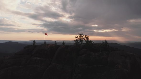 Thumbnail for Aerial View of the Red Flag on Top of the Rock in the Siberian Nature Reserve Stolby