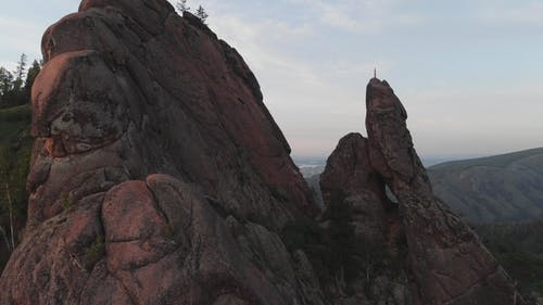 Aerial View of the Red Flag on Top of the Rock in the Siberian Nature Reserve Stolby