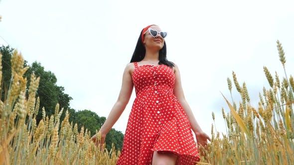 Thumbnail for Beautiful Girl in Red Retro Dress Walking in Golden Wheat Field