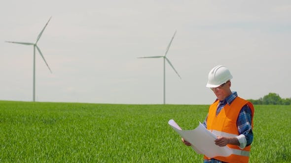 Thumbnail for Engineer Analyzing Plan While Looking At Windmill Farm. Eco Energy Concept