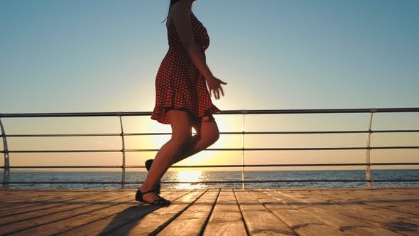 Thumbnail for Young Woman in Retro Short Dress Running on Wooden Embankment Near Sea. Girl Walking at Sunrise or