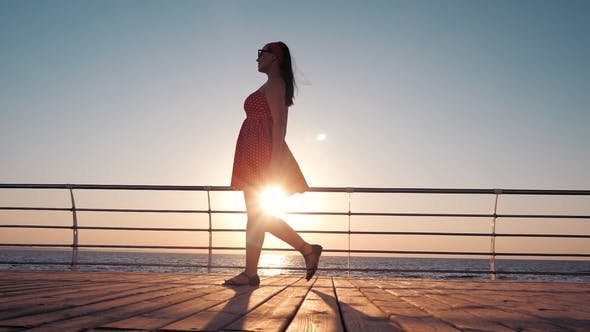 Thumbnail for Young Woman Stepping on Wooden Embankment at Sunrise