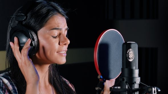 Thumbnail for Young Beautiful Brunette Woman Recording Voice, Song or Album in Professional Studio. Girl Sings