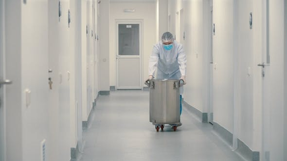 Thumbnail for Worker in Protective Uniform Pushing the Barrel Through Corridor in Laboratory