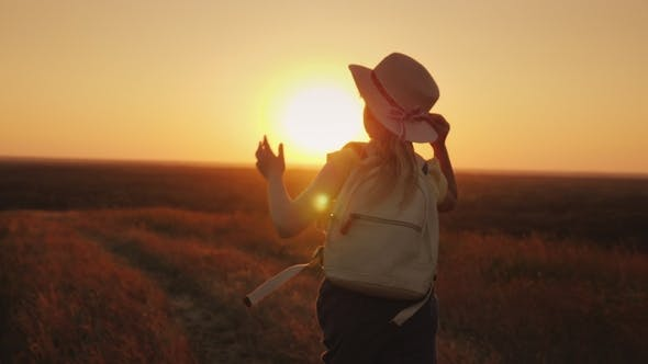 Cover Image for Girl in a Straw Hat Runs Down the Hill at Sunset