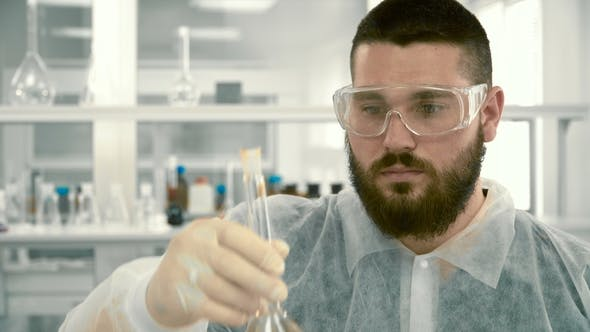 Laboratory Assistant Mixing Red Liquid in a Flask