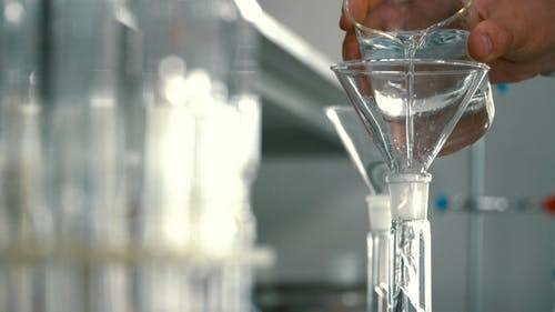 Chemist Pouring Alcohol Into a Flask Through Funnel