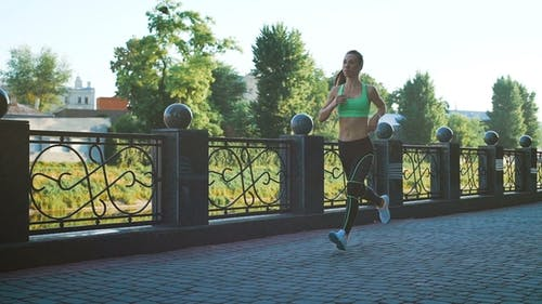 Active Woman Jogging Running in Sunny City Park