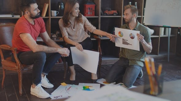Thumbnail for Startup Team Discussing Business Plan Documents at Floor in Office