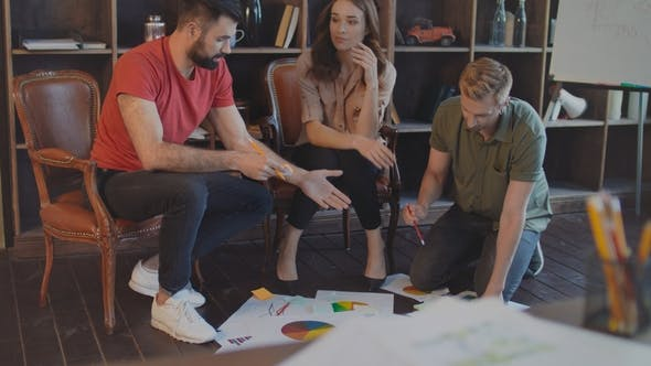 Thumbnail for Creative Team Discussing Business Strategy Documents on Floor in Office