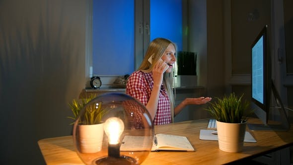 Thumbnail for Happy Female at Computer Talking on Smartphone. Cheerful Amazed Blond Woman in Checkered Shirt