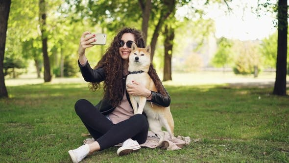 Cheerful Blogger Pet Owner Is Taking Selfie with Her Dog