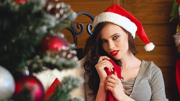 Happy Amazed Woman in Santa Hat and Smiles. Pretty Brunette with Long Dark Hair and Santa Clause Cap