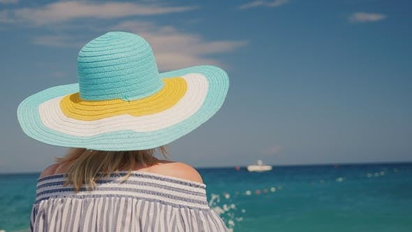 Thumbnail for A Woman in a Hat Looks at the Azure Sea. Dream Vacation Concept