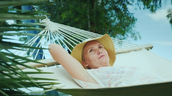 Thumbnail for Young Woman in Hat Is Resting in a Hammock