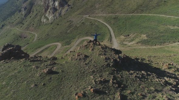 Thumbnail for Hiker Man Stands on Top of Mountain Over Serpentine Road with Raised Hands Aerial View