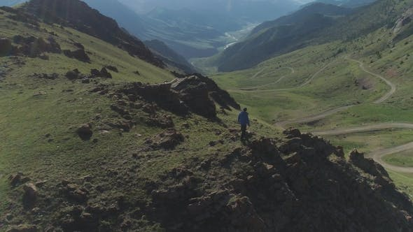 Thumbnail for Hiker Man Stands on Top of Mountain Peak Over Serpentine Road in Sunny Summer Day