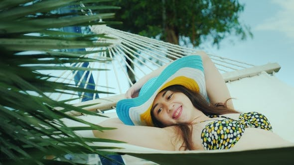 Thumbnail for A Cute Brunette in a Wide-brimmed Hat and in a Bikini Enjoys Relaxing in the Seaside Resort, Smiling