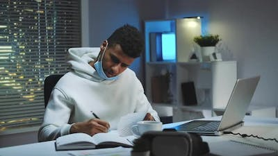 Mixedrace Man with Medical Mask Signing Documents in Home Office