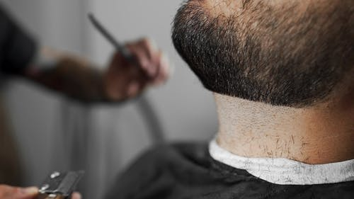 Tattoed Barber Shears the Customer's Beard By Using Trimmer at the Barber Shop, Man's Haircut