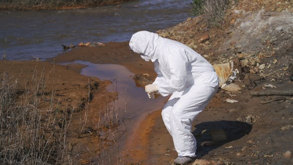 The Scientist in a Chemical Protective Suit Examines the Samples in the Contaminated Area. Biohazard