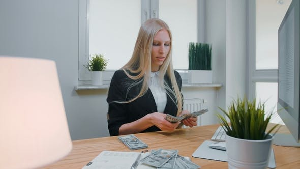 Thumbnail for Female Counting Money at Office Workplace. Beautiful Young Blond Woman in Business Suit Sitting in