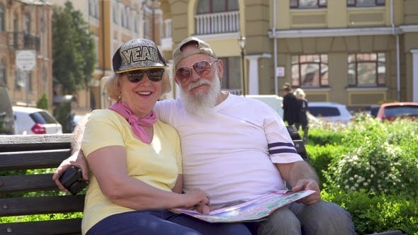 Thumbnail for Happy Senior Couple with Map on Knees Sit on Bench in City and Smiling To Camera