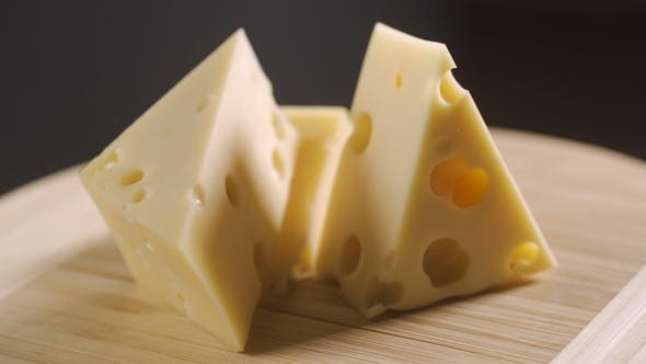 Thumbnail for Cheese, Cut Into Pieces on a Wooden Plate. Rotates Against a Gray Background