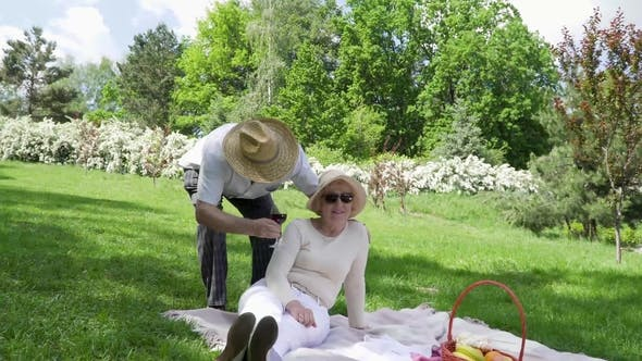 Thumbnail for Senior Man in Hat Bring a Glass of Wine To His Lovely Wife