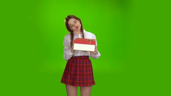 Thumbnail for Girl Holds a Gift in Her Hands and Is Pleased. Green Screen
