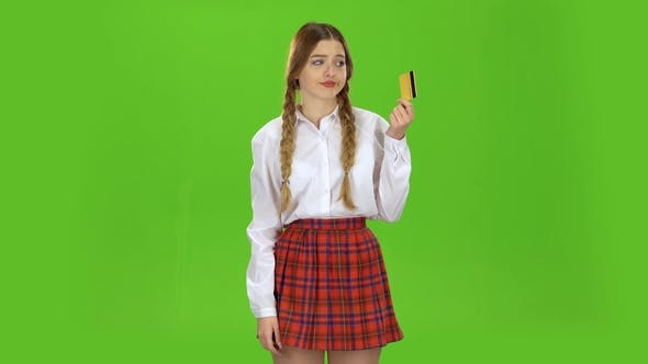 Thumbnail for Schoolgirl with a Credit Card in Her Hands Is Sad. Green Screen