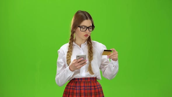 Thumbnail for Girl in Glasses Dials Numbers on the Phone with a Gold Card. Green Screen