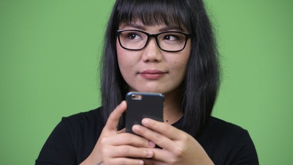 Thumbnail for Beautiful Asian Businesswoman Thinking While Using Phone