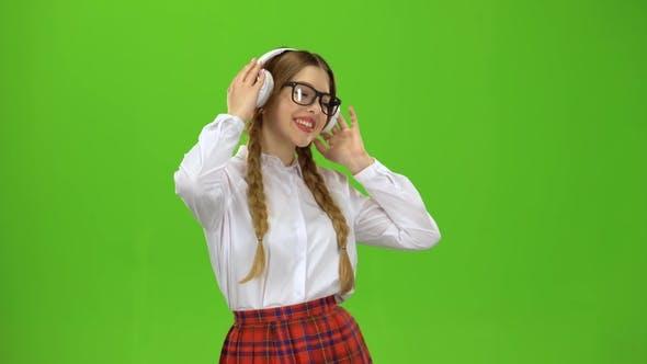 Thumbnail for Girl in Glasses Listens To Music on Headphones . Green Screen